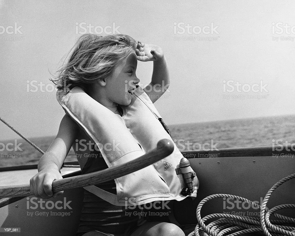 Girl in sailboat, wearing life jacket, holding rudder 免版稅 stock photo