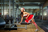 Girl in Santa costume doing exercises with dumbbells in the gym on Christmas Day.