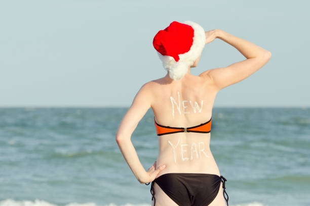 803fd583bf Girl in Santa hat and bathing suit looks into the distance. Inscription New  Year on