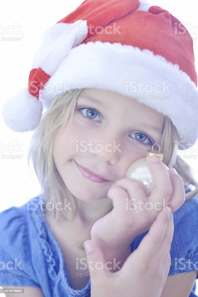 Girl in Santa Hat holding a bauble stock photo
