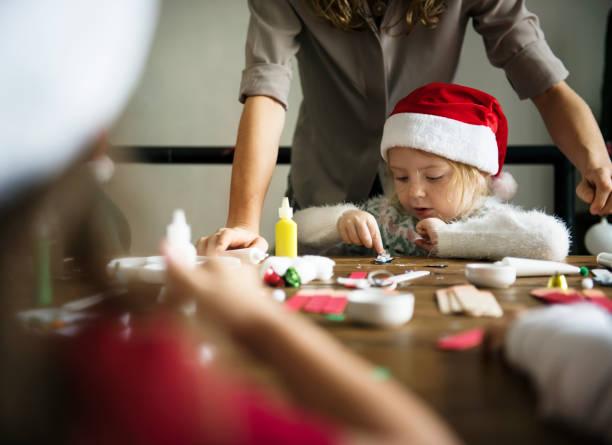 mädchen in ein diy projekt weihnachtsmütze - kindergarten workshop stock-fotos und bilder