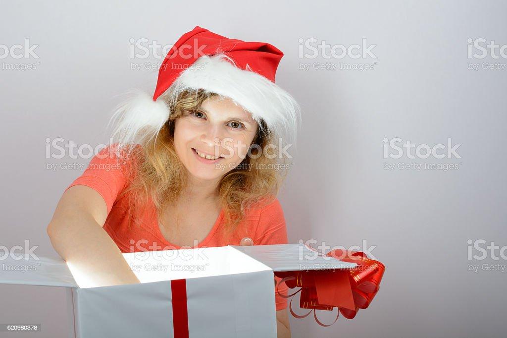 Girl in santa hat opening a box foto royalty-free