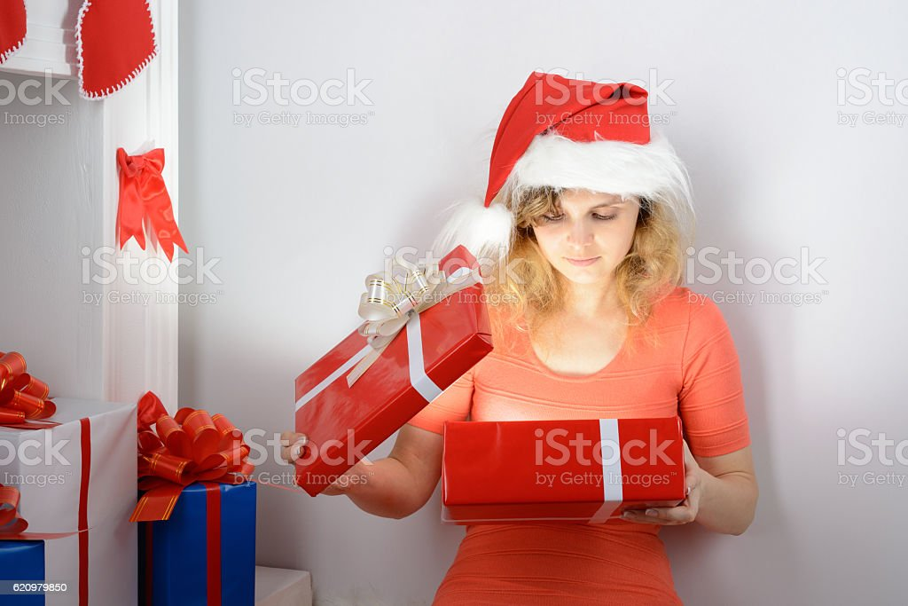 Girl in santa hat sitting by the fireplace foto royalty-free
