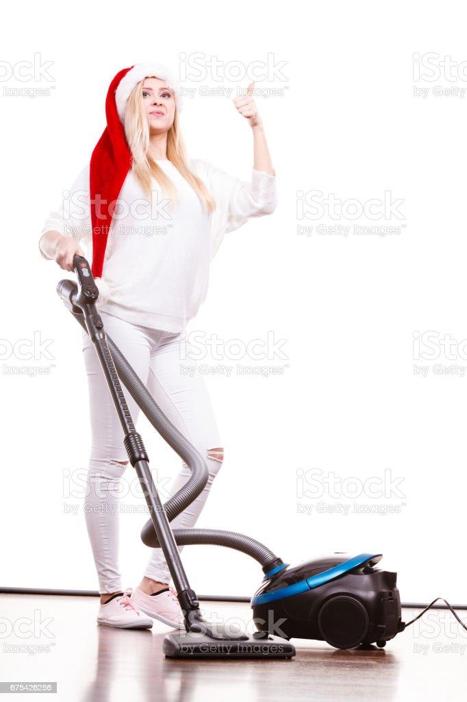 Girl in santa helper hat with vacuum cleaner royalty-free stock photo