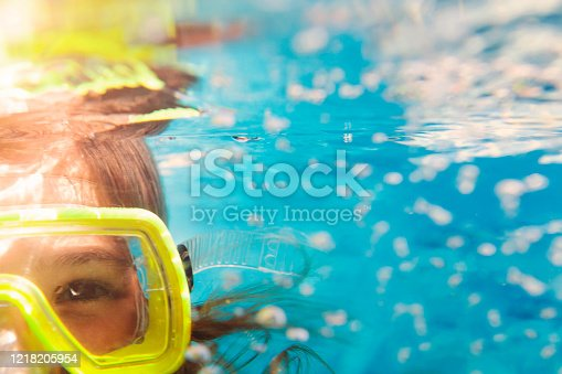 Little girl in colorful swimming mask smiling looking at camera under water