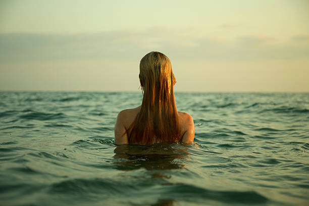 mädchen in wellen - fkk strand stock-fotos und bilder