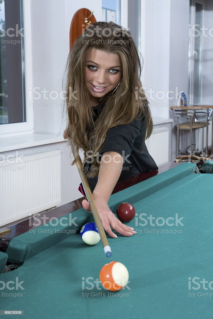 Girl in short skirt playing snooker royalty-free stock photo