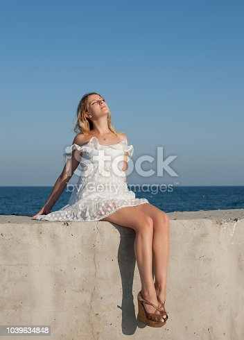 Girl in short white sleeveless dress sunbathes with skirt lifting above the knees. Young woman in white short dress sitting on seafront with eyes closed leaning on hands