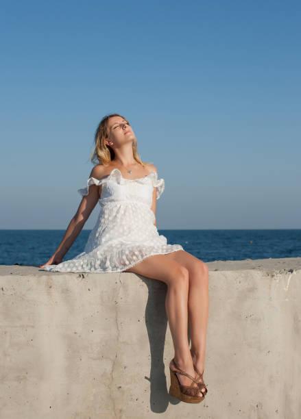 7b1c7397e9 Girl in short white sleeveless dress sunbathes with skirt lifting above the  knees stock photo