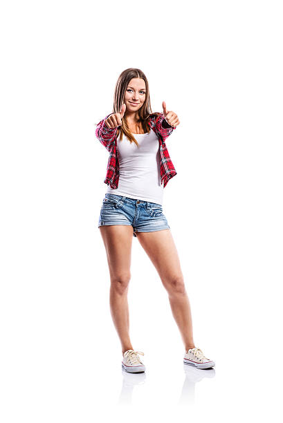 girl in shorts and checked shirt, thumbs up, isolated - jean shorts stock photos and pictures