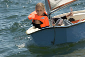 Teenage girl with life jacket sailing in small sailing vessel.