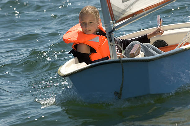 Girl in small sailing boat Teenage girl with life jacket sailing in small sailing vessel. individual event stock pictures, royalty-free photos & images