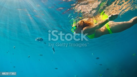 istock Girl in snorkeling mask dive underwater with coral reef fishes 682517352