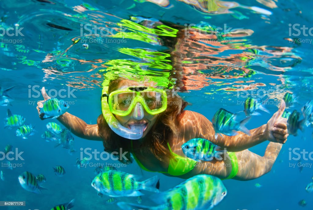 Girl in snorkeling mask dive underwater with coral reef fishes - foto stock