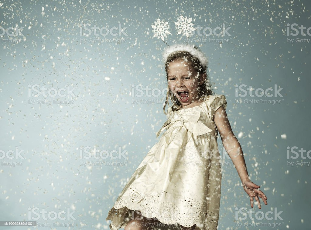 Girl (6-7) in snow, mouth open photo libre de droits