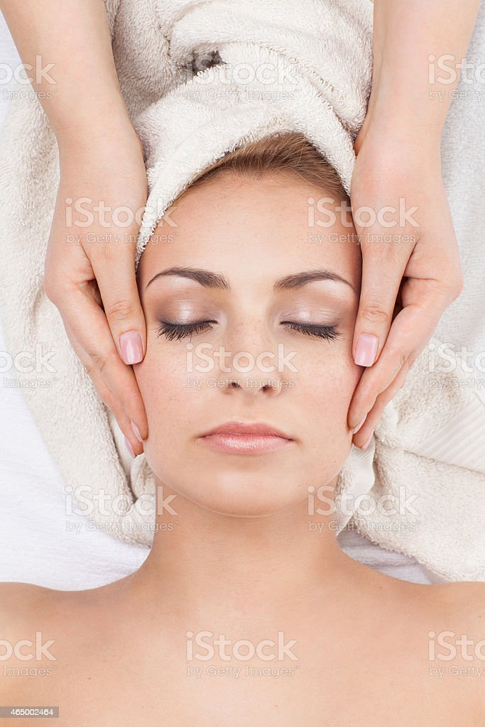 Girl in spa salon receiving face massage stock photo