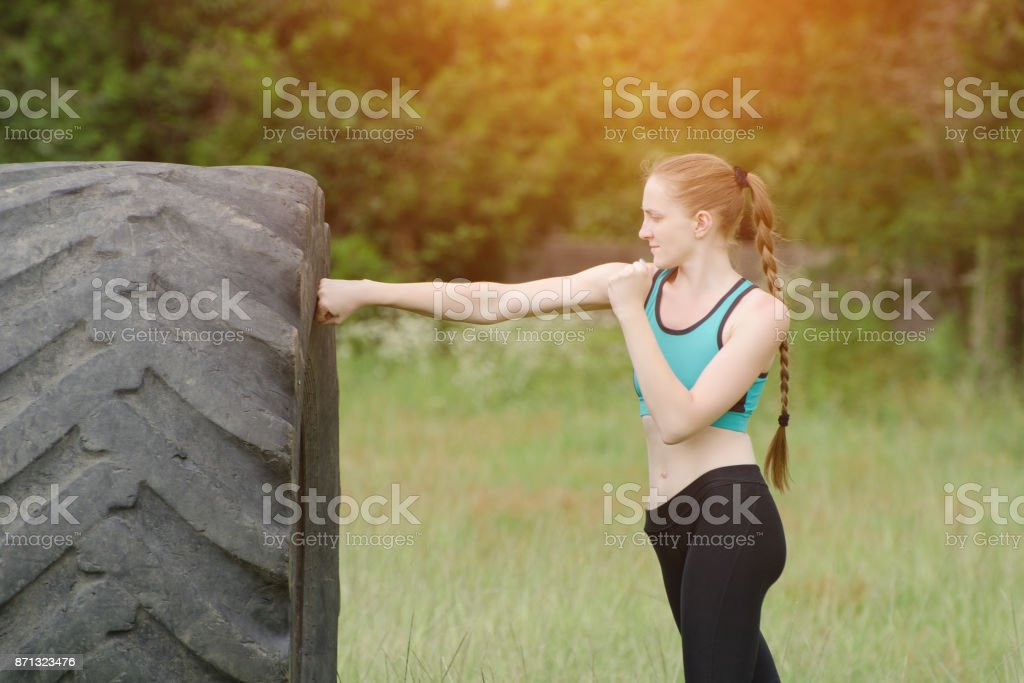 Girl in sportswear boxing with the tire. street workout