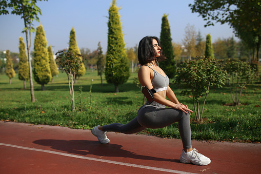 girl in sportswear doing a warm-up before jogging. Woman in summer in the running track. With headphones listening to music motivates yourself to run. The concept of a healthy lifestyle or hobby.
