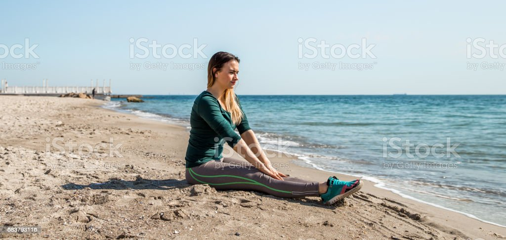 Girl in sportswear fitness by the sea listening stock photo