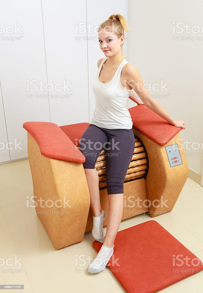 Girl in sportwear using relax massage equipment healthy spa salon royalty-free stock photo