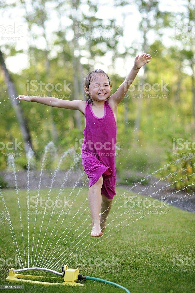 Girl in Sprinkler stock photo