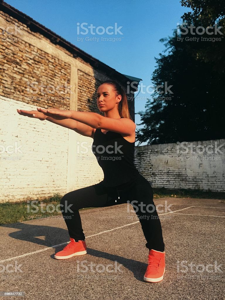 Girl in squat position on the public court royalty-free stock photo