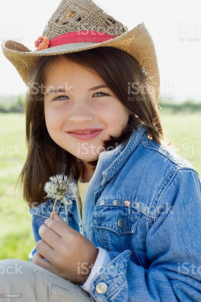 Girl in straw hat holding dandelion royalty-free stock photo