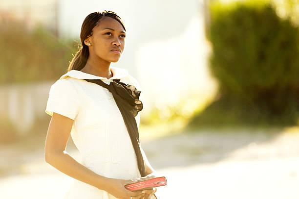 Girl in street holding black book stock photo