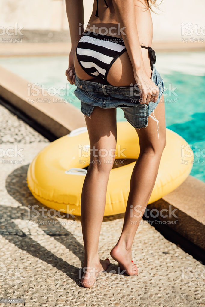 girl in striped bikini pulls off shorts near the pool stock photo