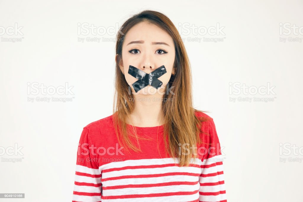 Girl in studio with black tape over her mouth stock photo
