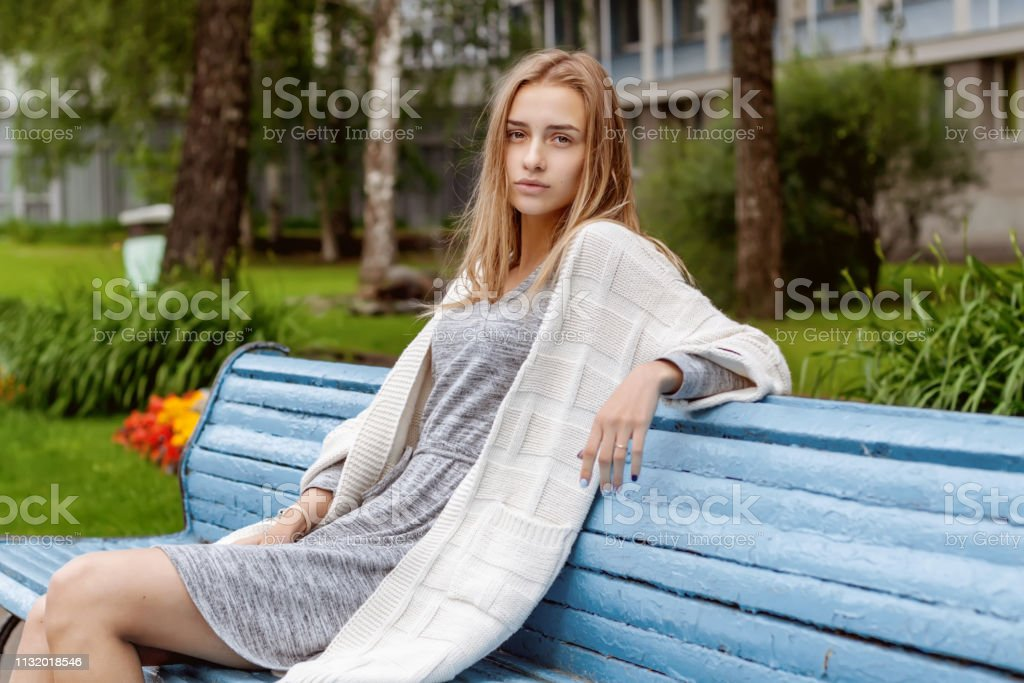 A girl in stylish clothes and beautiful looks is sitting on a blue...