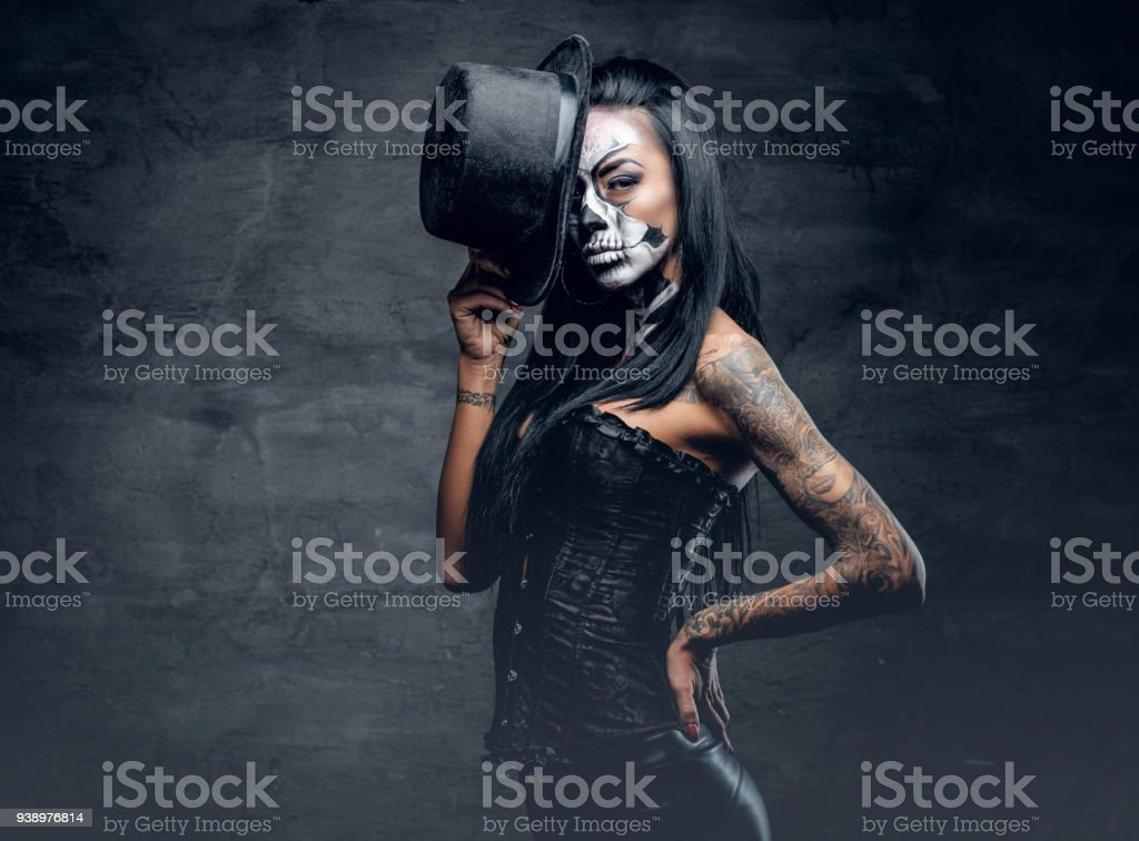 A girl in stylish top hat with skull make up. stock photo