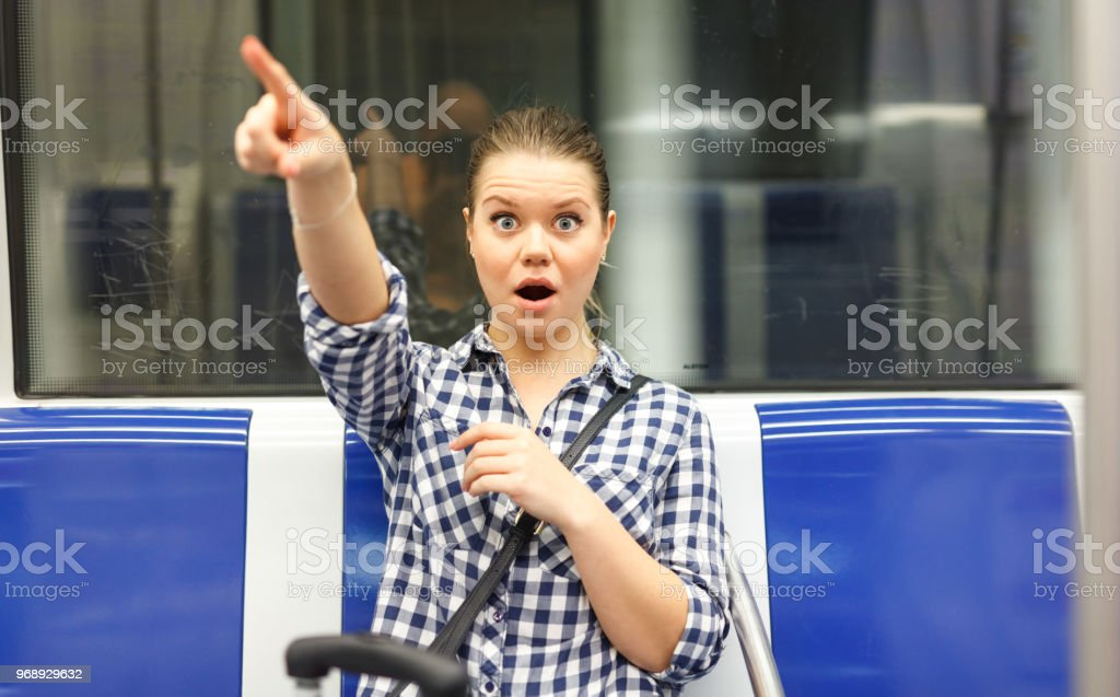 Girl in subway car pointing at something stock photo