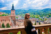 Girl in sunglasses at panoramic view on Stiftskirche Collegiate church and cityscape with Black forest in Old city of Baden Baden in Baden Wurttemberg, Germany. Young woman and scenery of German town.