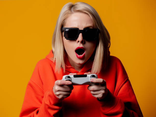 girl in sunglasses keen plays with a joystick stock photo