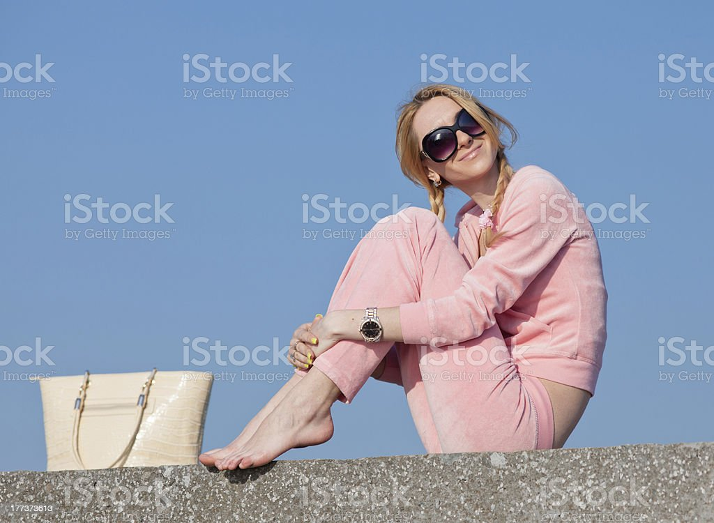 Girl in sunglasses with bag on background of sky royalty-free stock photo