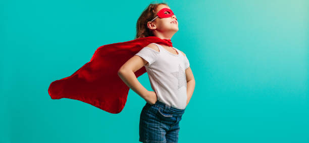 Girl in superhero costume Girl child wearing red superhero costume standing with her hands on hips in studio. Girl in red cape and mask looking away on blue background. girl power stock pictures, royalty-free photos & images