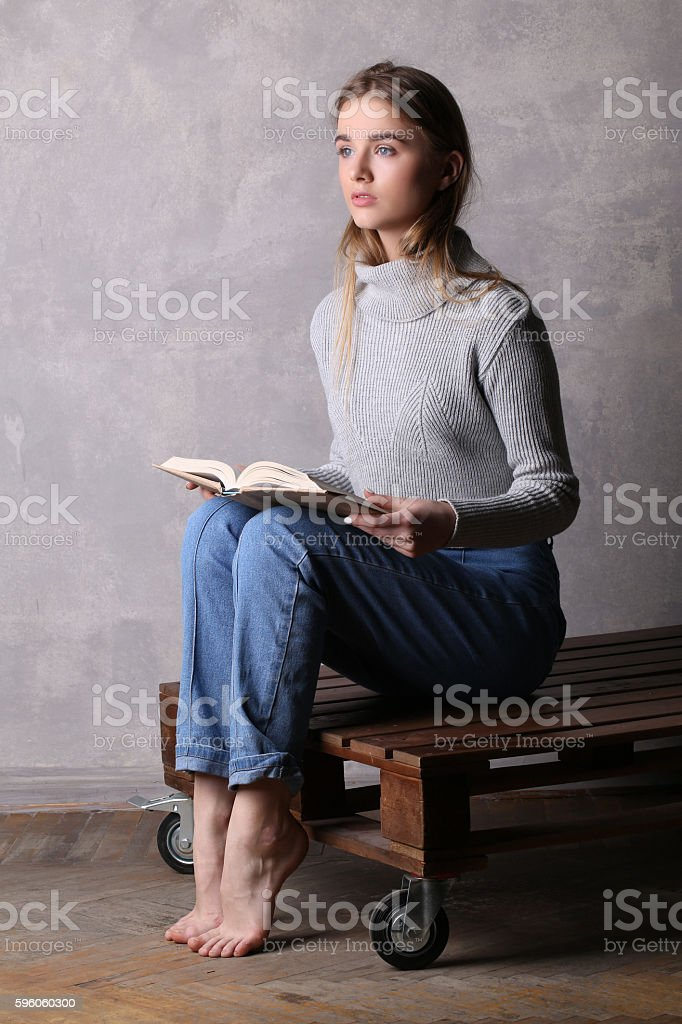 Girl in sweater holding a book. Gray background royalty-free stock photo
