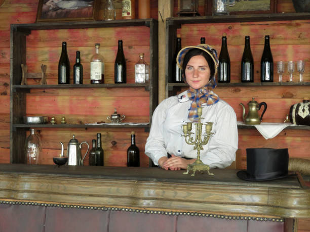 Girl in the american saloon of the 19th century Moscow, Russia - August 2018: Bartender woman stands behind the counter of the american saloon of the 19th century during the festival of historical reconstruction