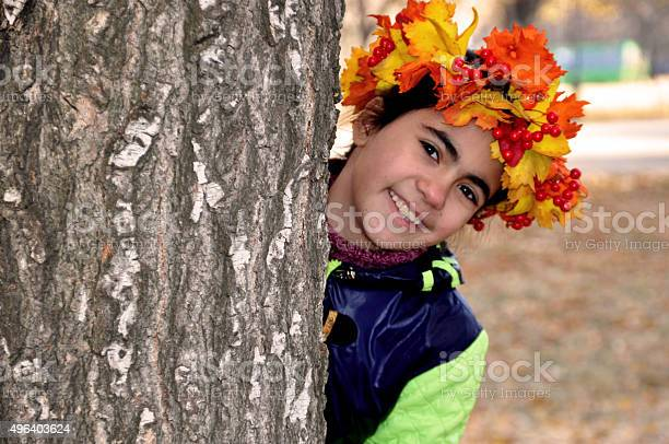 Photo of Girl in the autumn wreath looks out from behind tree