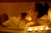 Girl in the bath having a glass of red wine,, candle lit