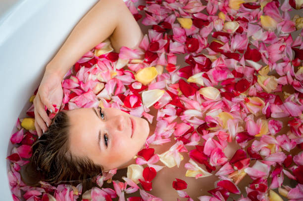 girl in the bathroom with rose petals, close up portrait stock photo