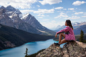 Young girl enjoying the beautiful Canadian Rockies Landscape view during a vibrant sunny summer day. Taken in Peyto Lake, Banff National Park, Alberta, Canada.