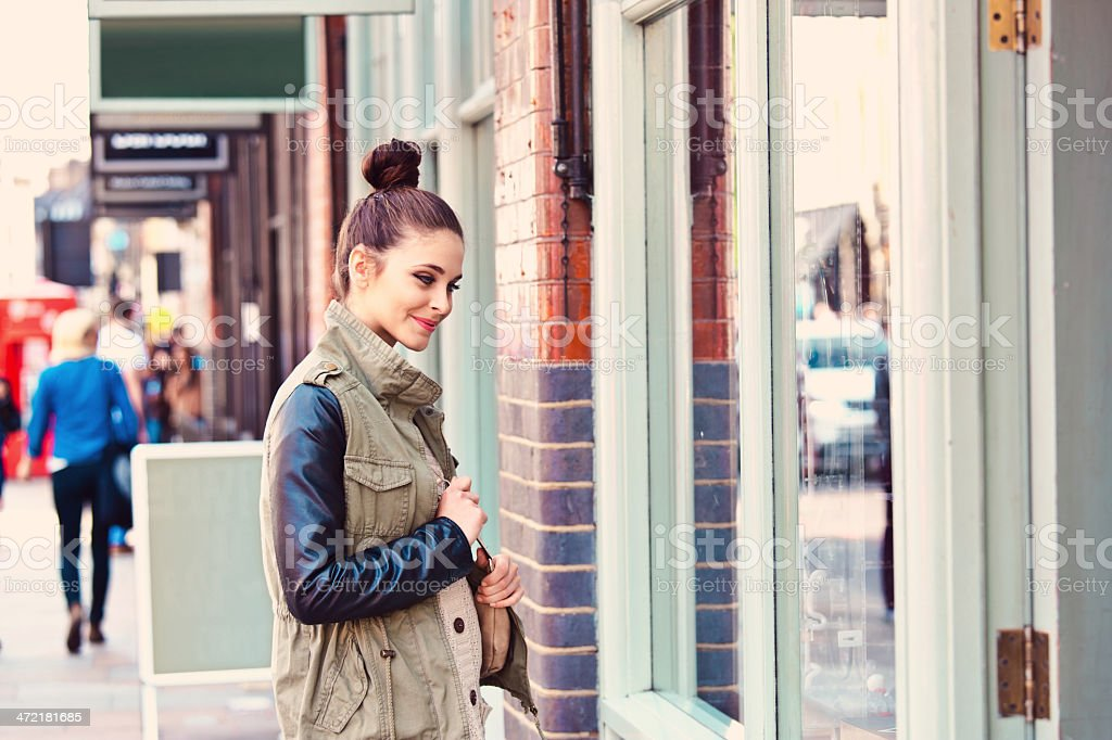 Girl in the city Young smiling woman standing at a shopwindow in the city. 20-24 Years Stock Photo