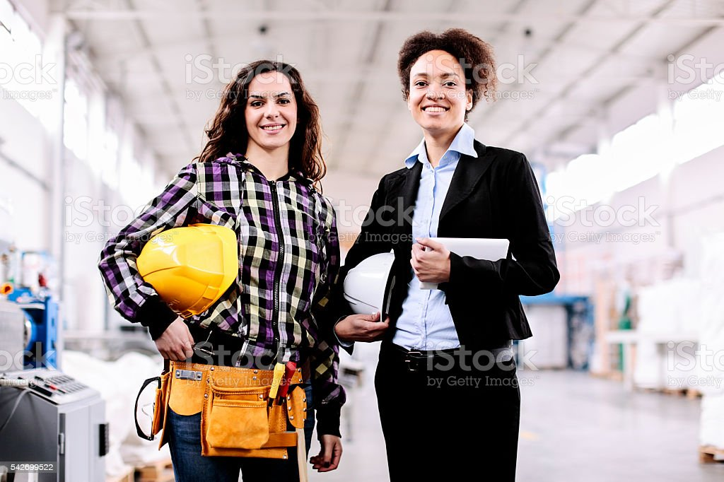 Girl in the factory with her female boss stock photo