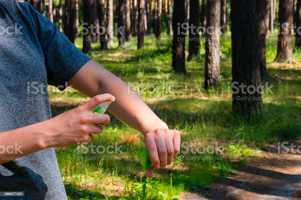 girl in the forest uses the spray against mosquitoes стоковое фото