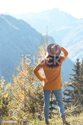 girl in the hat stands on the background of mountains
