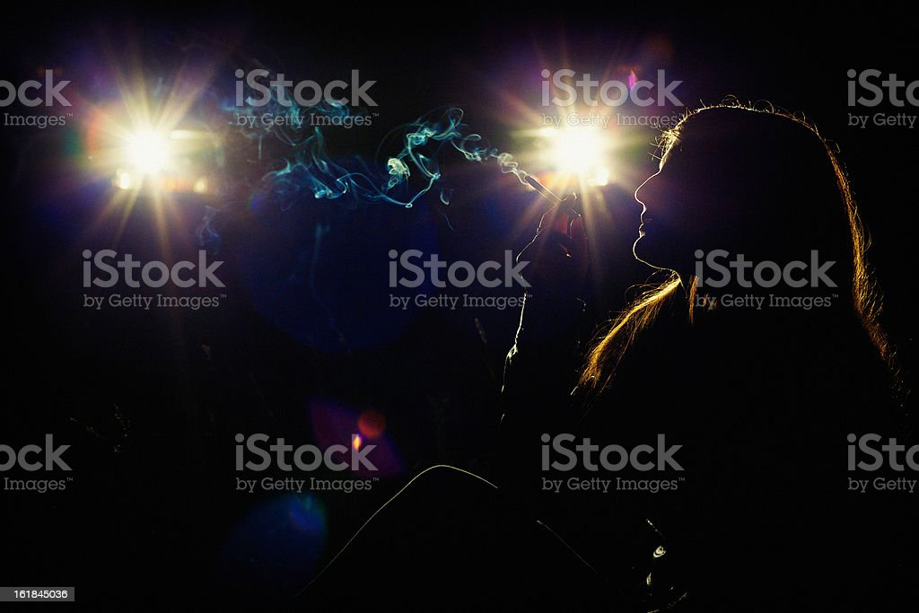 Girl in the headlights of car with a cigarette royalty-free stock photo