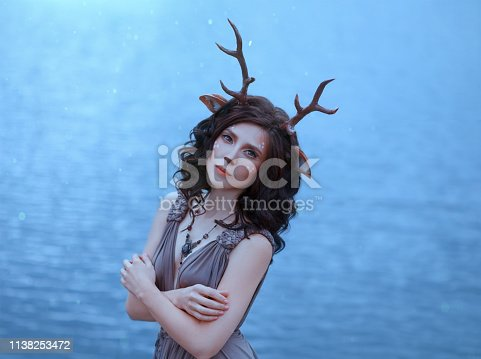 girl in the image of a faun, costume and make-up of a deer, a fantastic character of the spirit of forest in brown dress, portrait photo of a sad lady on background of magical lake, blue cool shades.