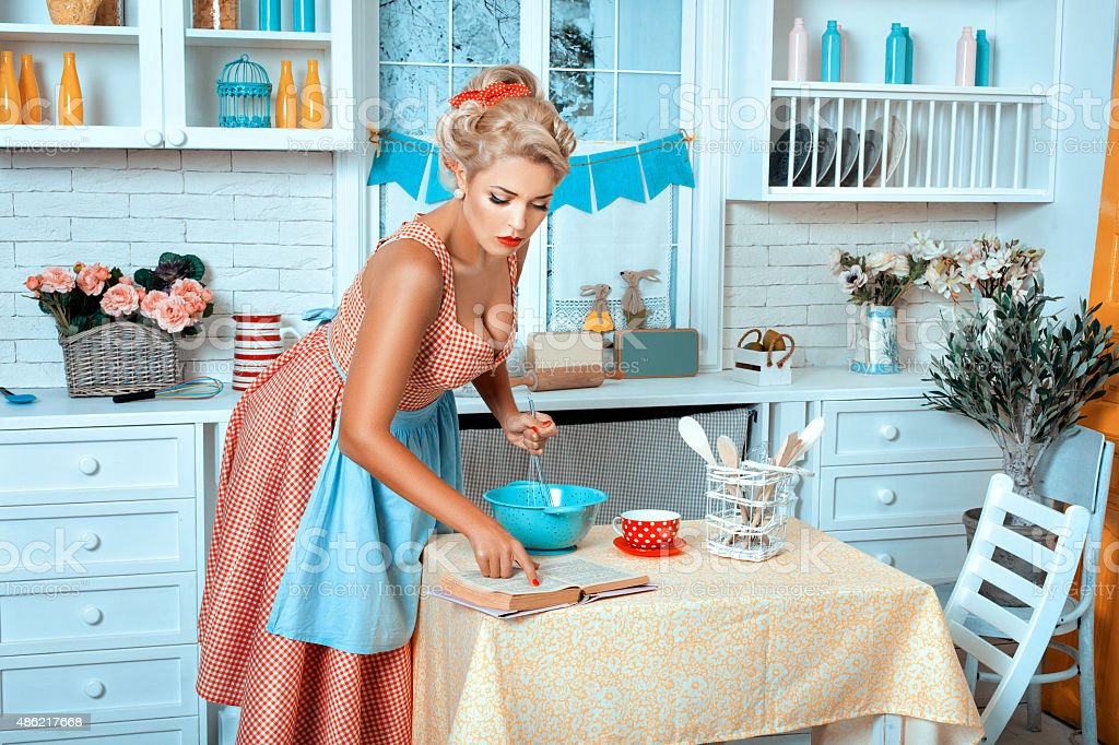 Girl in the kitchen reading recipe  book. stock photo